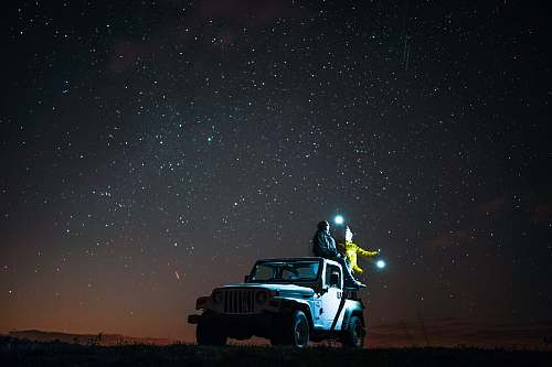 stars person sitting on top of wrangler under starry sky jeep