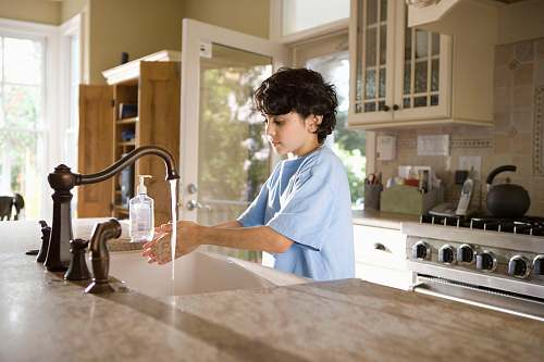 human boy in blue polo shirt standing in front of sink sink