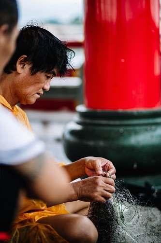 human man fixing fish net finger
