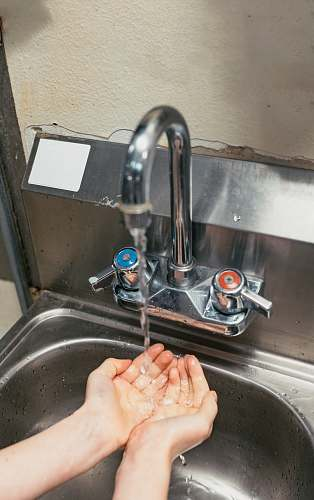 human person washing hand on stainless steel faucet sink faucet