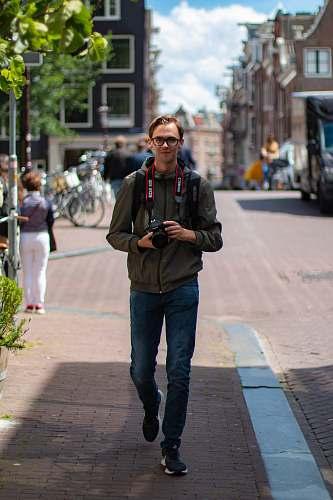 clothing man holding black DSLR camera standing on sidewalk during daytime footwear