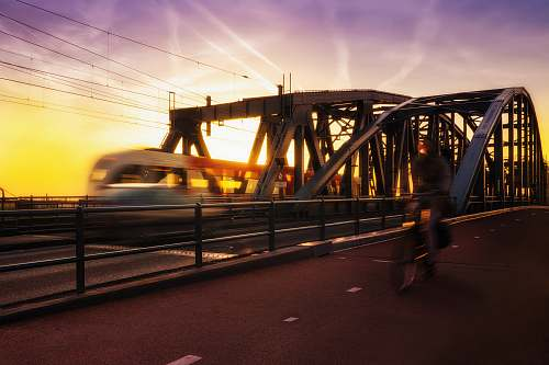 architecture time-lapse photography of biker passing road beside trail during golden hour bridge