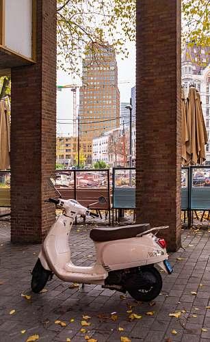 machine white motor scooter parked near pillars wheel