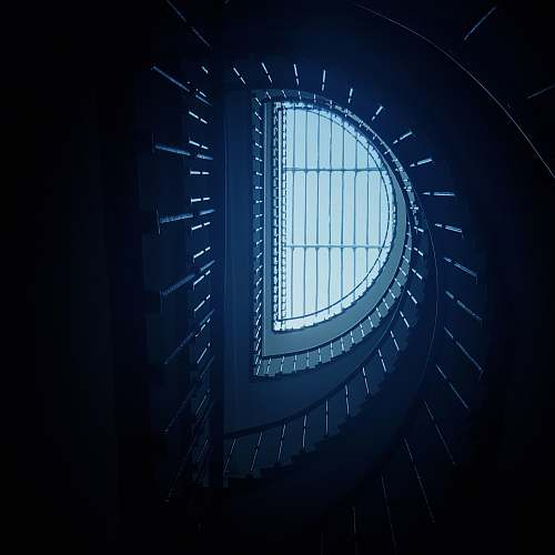 building low-angle photography of spiral stairs skylight