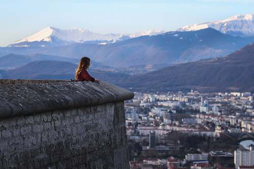 view woman standing near high rise buildings and mountains during daytime grenoble