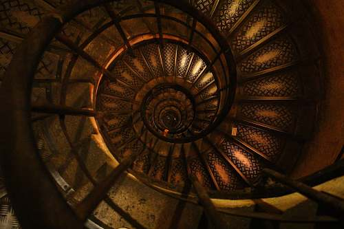 stairs A worn spiral staircase with dark wood and faded designs spiral