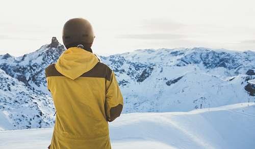 human man facing snow covered mountain people