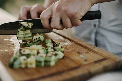 sushi person slicing on the wooden board vegetable