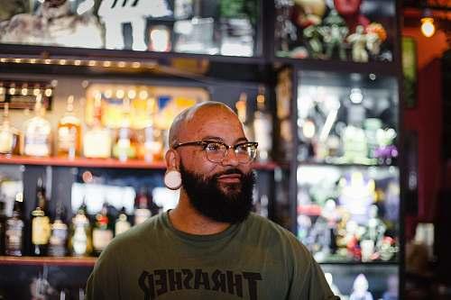 human man in gray Thrasher crew-neck shirt standing near rack of bottles people
