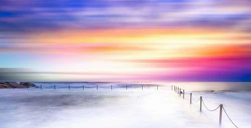 water sea of clouds beside metal rail ocean
