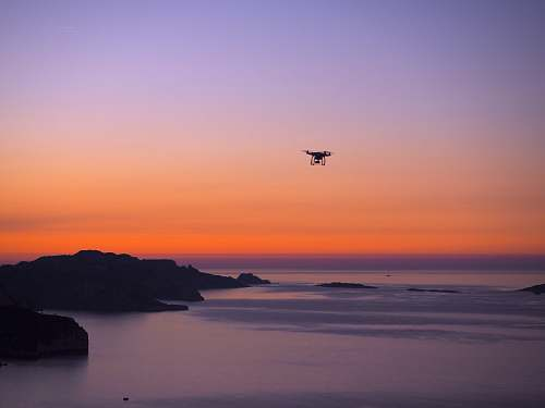 dawn silhouette photo of drone on seashore sunset