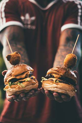 people person holding two cheese hamburgers person