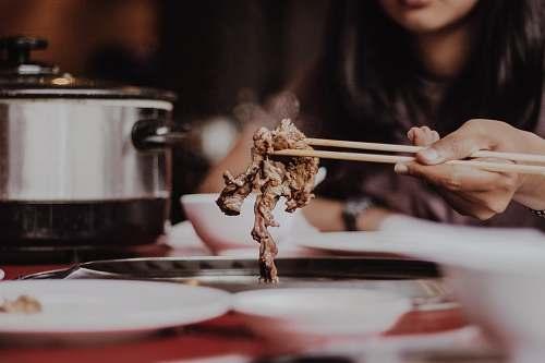 meal woman holding beige chopsticks meat