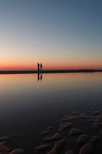 sunset two person standing on beach dock wissant