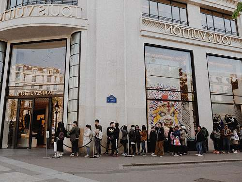 person people queuing beside Louis Vuitton store people
