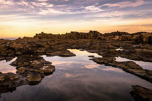 rocks calm body of water and overlooking mountain bombo quarry