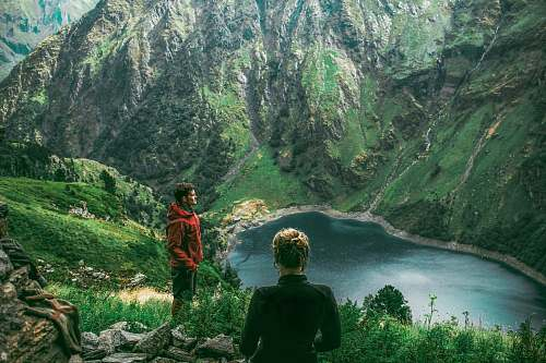 outdoors woman and man standing on mountain near creek during daytime mountain