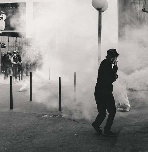 human grayscale photo of man near smoke lyon