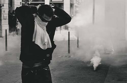 human man standing and covering his face using shirt smoke