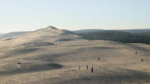 nature people gathered on desert under gray sky sand