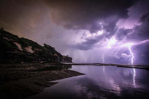 thunderstorm lightning near body of water and rock formation nature