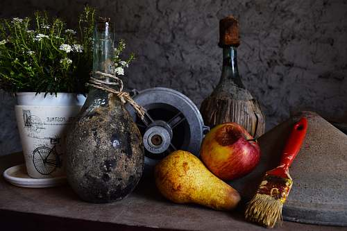 fruit vase beside flower pot and fruits on table produce