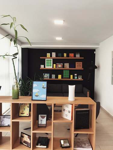 table black iPad near lucky bamboo in vase on brown wooden shelf inside room furniture