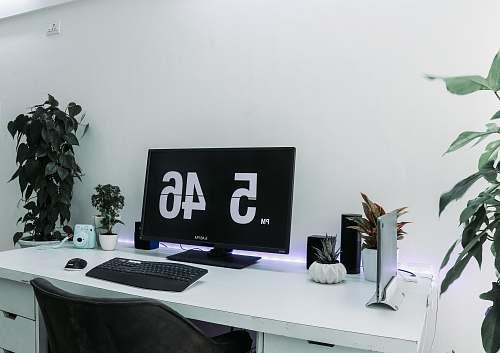 table turned on flat screen monitor displaying 5:46 furniture