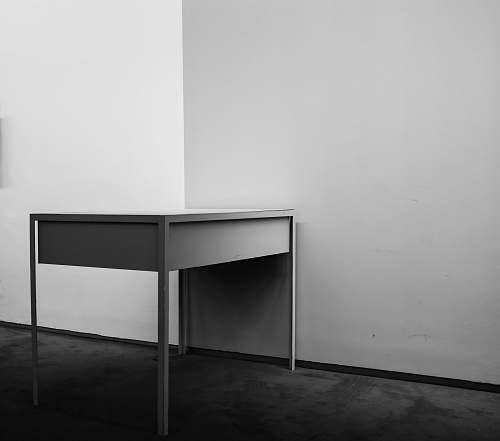 furniture white wooden desk beside white wall black-and-white