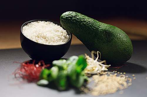 plant avocado fruit near cooked rice and sliced green bell pepper avocado