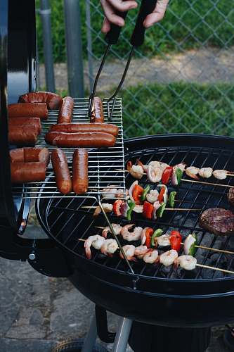 hot dog grilled sausage and meat beside gray chain-link fence bbq