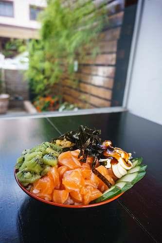 plant kiwi, cucumber, fish meat, banana, and nori salad on plate patos de minas