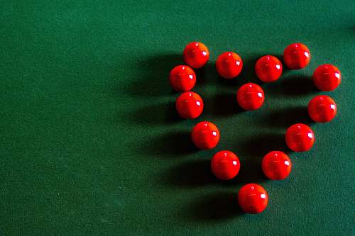 table red round beads on green textile indoors