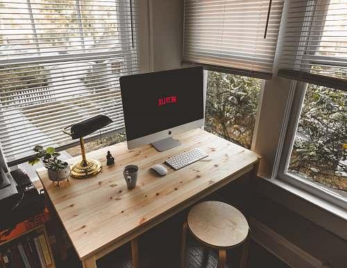 desk silver iMac, Magic Mouse, and wireless keyboard on desk neaar windows home decor