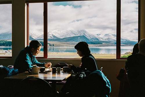 human man an woman having breakfast with the view of mountain restaurant