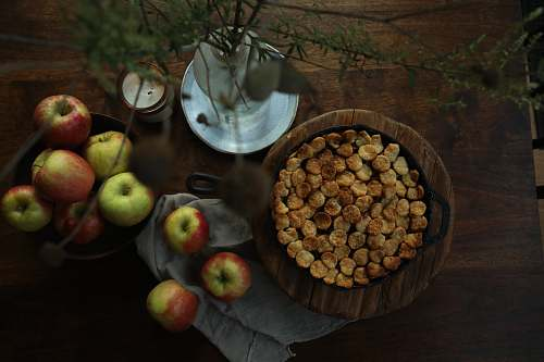 apple brown round food on brown wooden round bowl beside green apple fruit on brown wooden table fruit