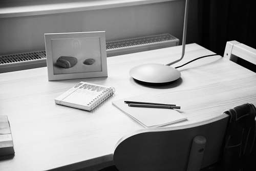 furniture notebook on desk near photo frame black-and-white