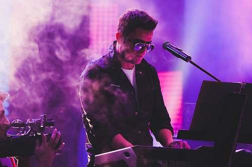 person man in black coat singing musician