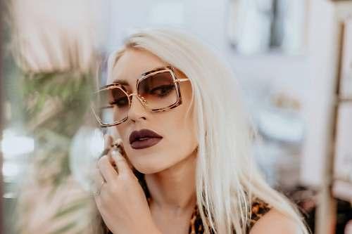 person woman wears dark brown matte lipstick and oversized sunglasses sunglasses
