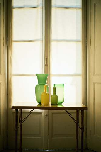 room photo of vases on top of table in front of window furniture