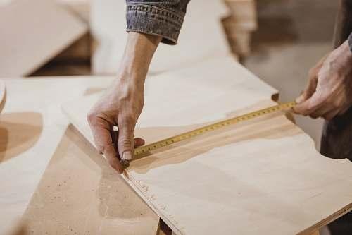 plywood person measuring brown board human