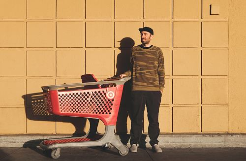 photo man standing near red and gray shopping cart free for commercial use images
