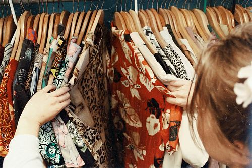 photo person holding assorted clothes in wooden hanger free for commercial use images
