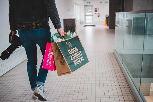 photo person walking while carrying a camera and paper bags free for commercial use images
