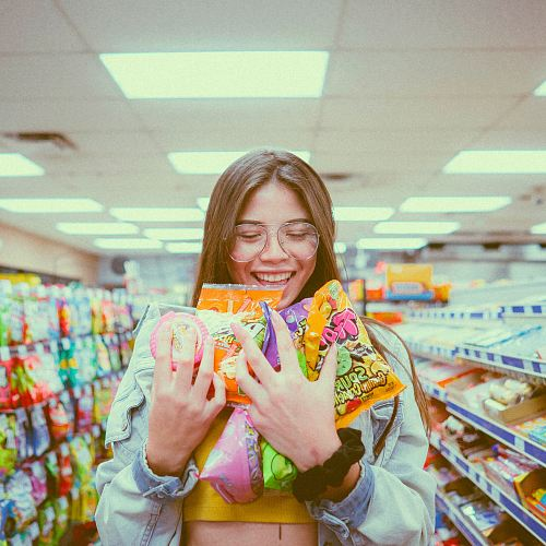 photo smiling woman holding pack of food inside grocery store free for commercial use images