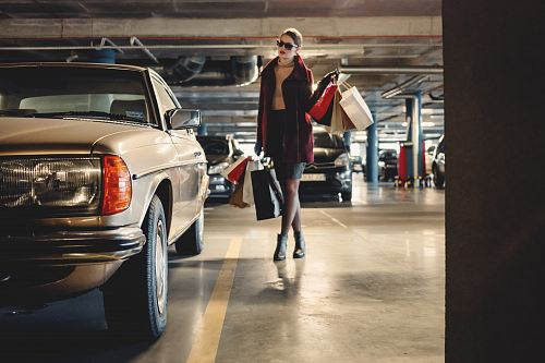 photo woman carrying shopping paper bags walking towards beige car inside parking lot free for commercial use images
