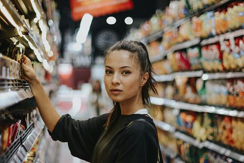 photo woman selecting packed food on gondola free for commercial use images