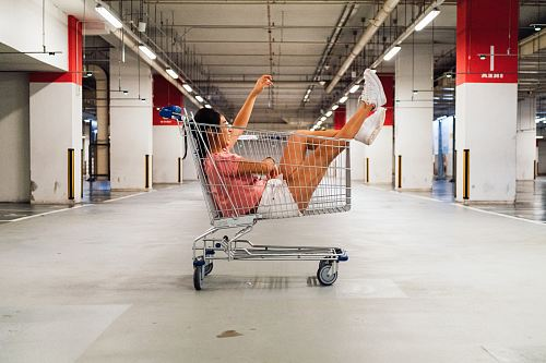photo woman sitting in shopping cart at parking lot free for commercial use images