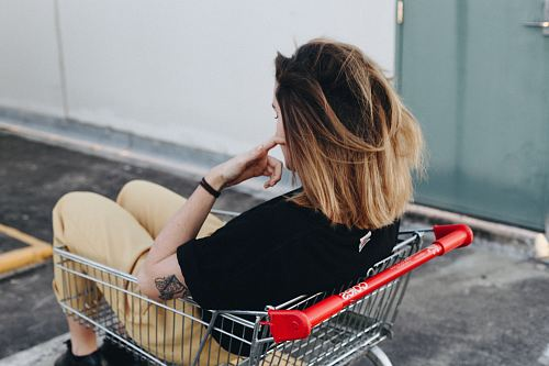 photo woman sitting on shopping cart near the wall free for commercial use images