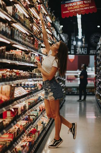 photo woman standing beside shelf free for commercial use images